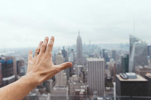 Men wearing ring stretches hand out over city skyline