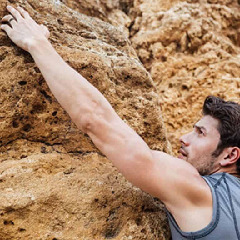 Man is rock climbing while wearing his ring