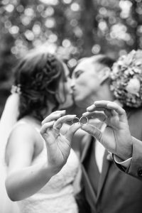 Married couple kiss as they hold out their wedding rings