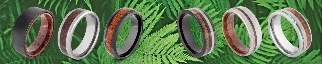 Selection of natural wood rings for men against backdrop of lush green fern leaves