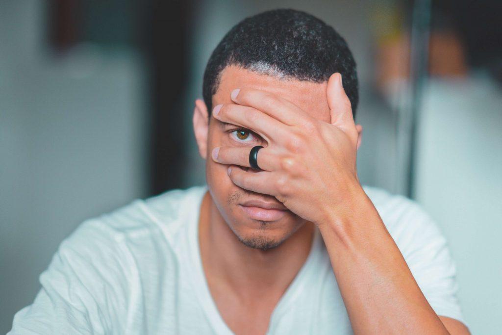 Man looks through fingers wearing black ring