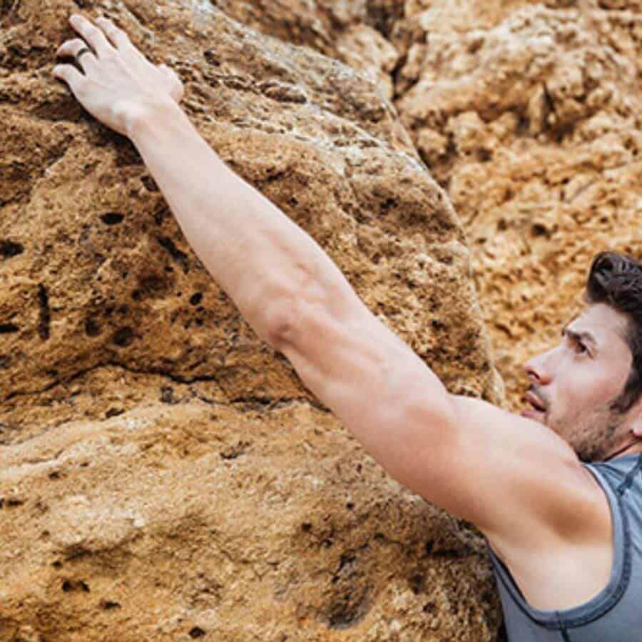 Man rock climbing showing his inspiring ring design
