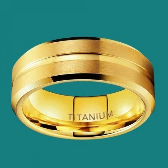 Gold titanium ring for men on teal background