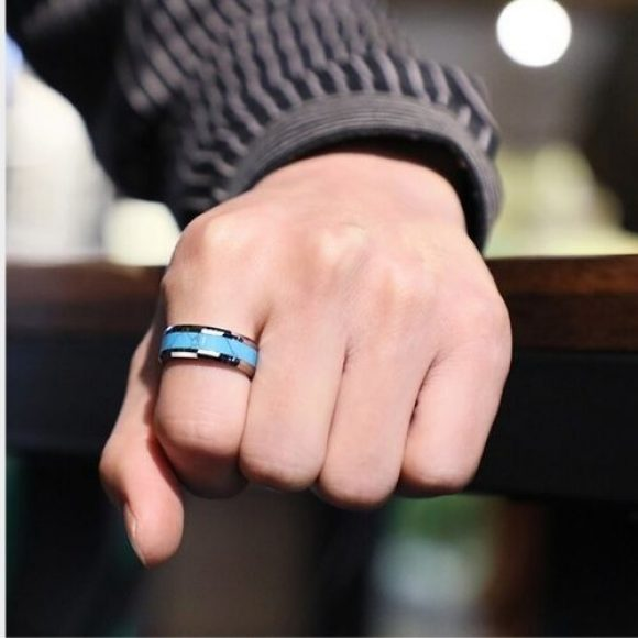 Man tries on his silver and blue tungsten ring